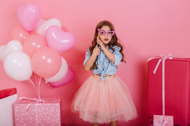 Cute surprised little girl with long brunette hair holding mask on face, looking to camera  on pink background royalty free stock photo