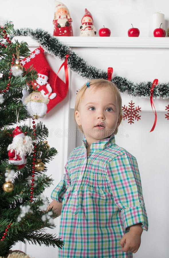 Cute surprised little girl stands near the Christmas tree stock photo