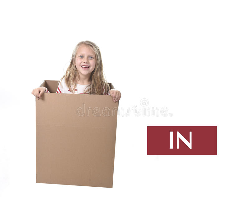 Cute and sweet blond hair child in cardboard box isolated on white background in learning english prepositions. And words language card set for education school royalty free stock images