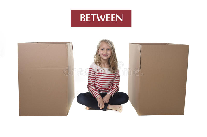 Cute and sweet blond hair child sitting between two cardboard boxes. Isolated on white background in learning English prepositions and words language card set royalty free stock photography