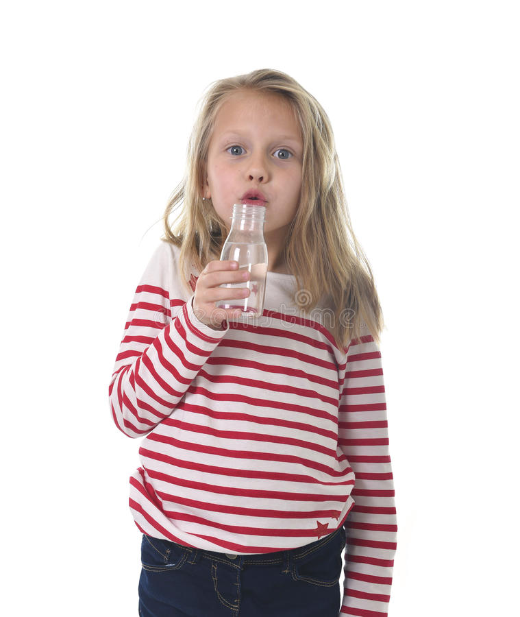 Cute sweet little girl with blue eyes and blond hair 7 years old holding bottle of water drinking stock images
