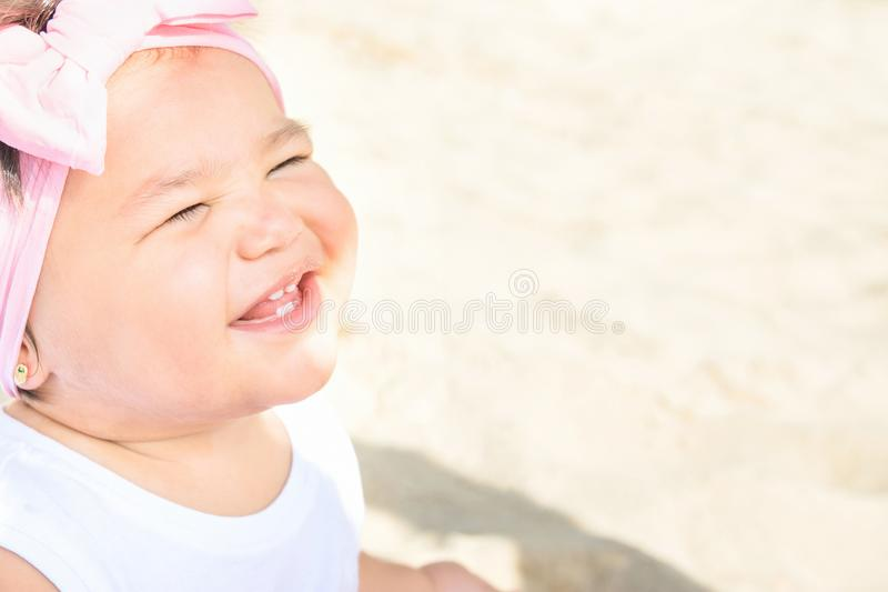 Cute Sweet 1 Year Old Baby Girl Toddler Sits on Beach Sand by Ocean Smiling. Sweet Face Expression. Bright Sunny Day. Parenting stock photos