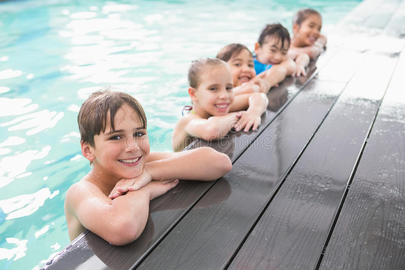Cute swimming class in the pool stock photography