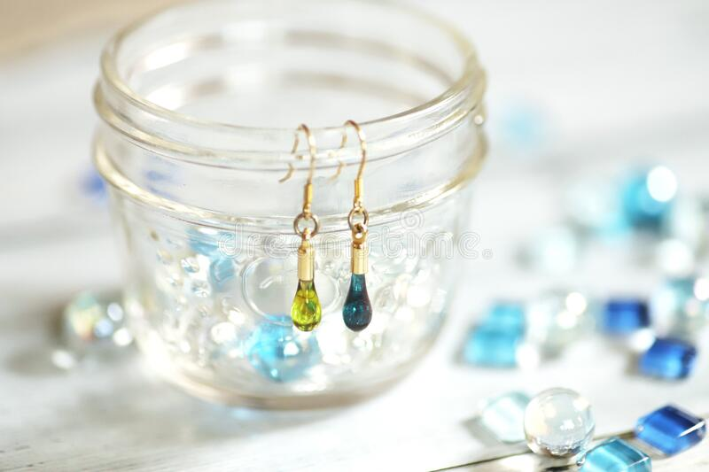 Cute teardrop-shaped earring made of glass and blue glass tiles stock photos