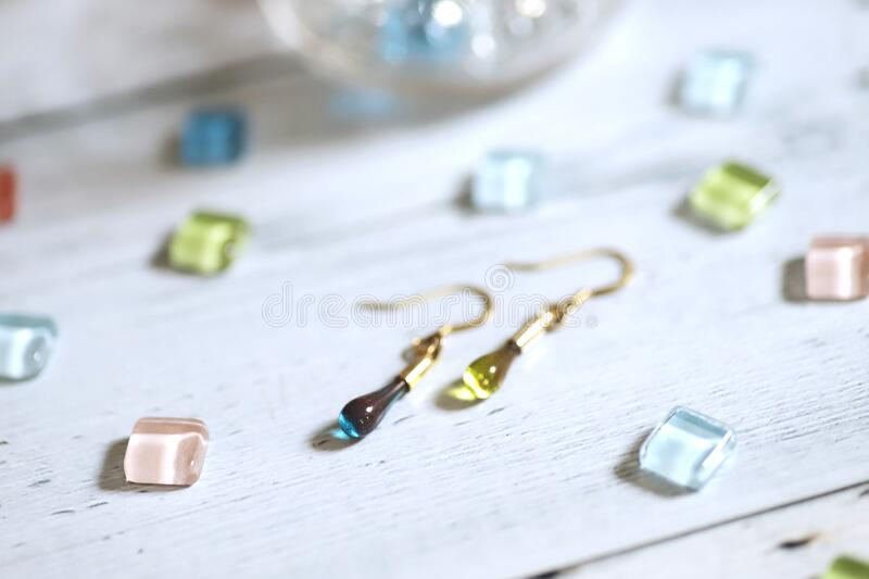 Cute teardrop-shaped earring made of glass and colorful glass tiles stock photo