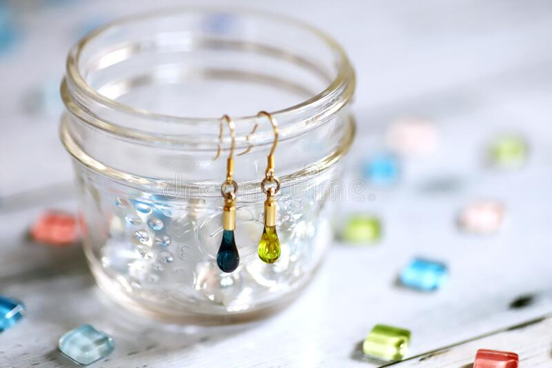 Cute teardrop-shaped earring made of glass and colorful glass tiles stock images