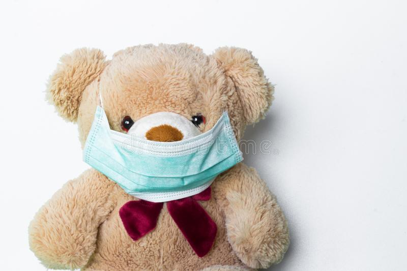 Cute teddy bear with face mask on his mouth. On white background stock photo