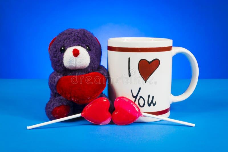 Cute teddy bear holding out a heart sitting next ot an stock photo