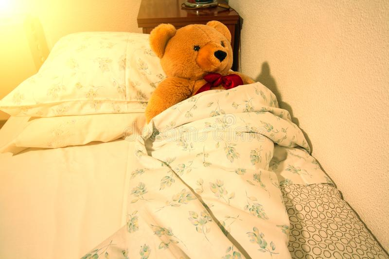 A cute teddy bear lies in bed covered with a blanket. The morning bright sun shines through the windows. Time to get up and go to. School or kindergarten, cosy stock images