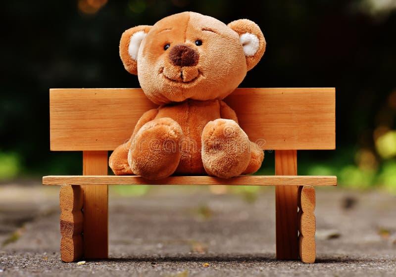 Cute teddy bear sat on a bench royalty free stock photography