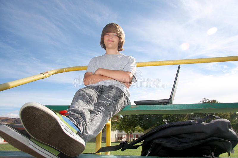 Cute Teen on Bleachers. Cute teen boy sitting on bleachers with his laptop and backpack royalty free stock photo