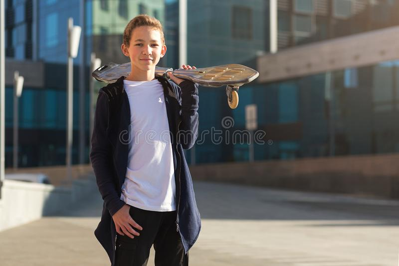 Cute teen boy with skateboard outdoors, standing on the street.  royalty free stock photo