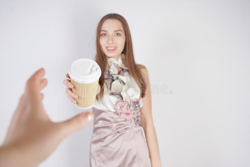 Cute teen caucasian girl in a pretty evening dress gives a paper Cup of coffee, treating the interlocutor and smiling, on a white stock image