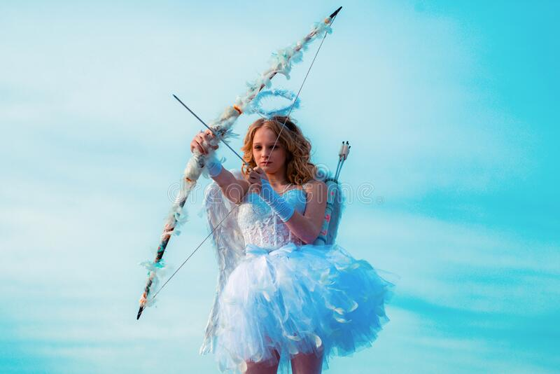 Cute teen cupid on the cloud - sky background. Lovely and cute youth. Lovely girl cupid with bow and arrow is ready to royalty free stock photography