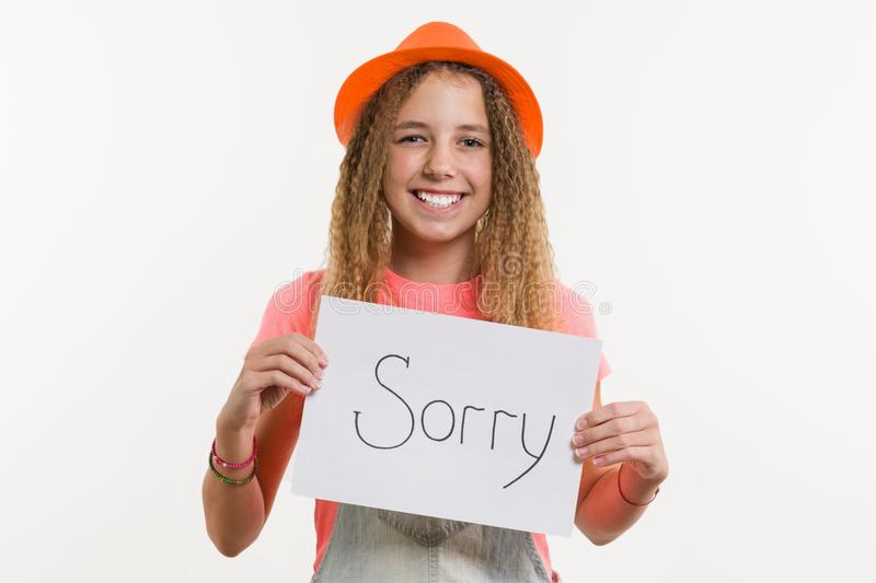 Cute teen girl character holding a sign with message sorry. On white background stock photo