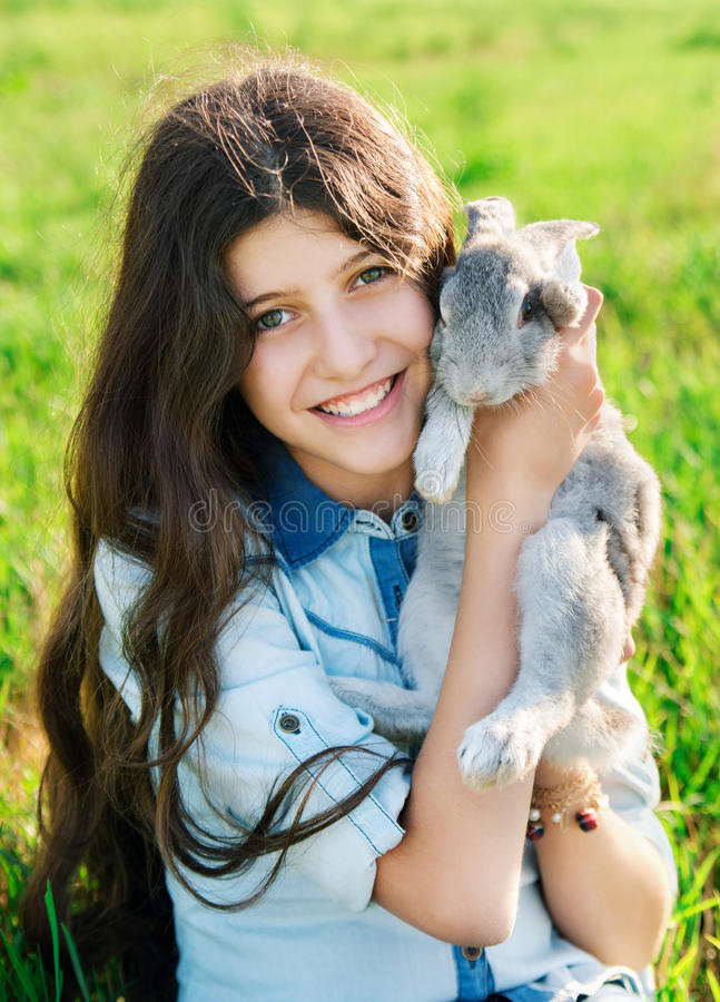 Cute teen girl with gray rabbit royalty free stock images