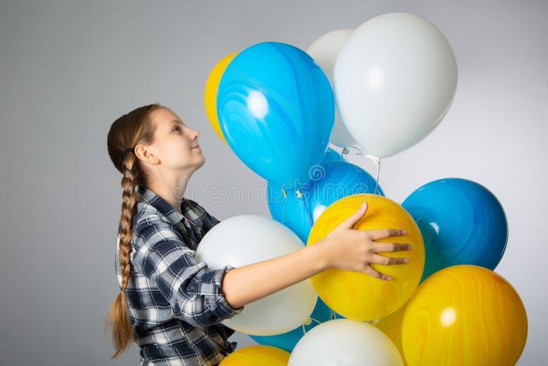 Cute teen girl holding a bunch of colorful balloons stock photos