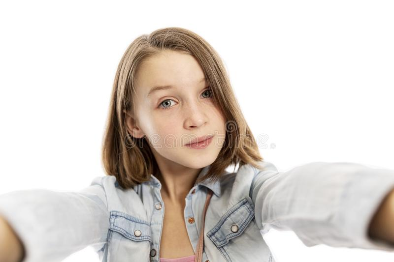 Cute teen girl makes selfie, white background royalty free stock photos