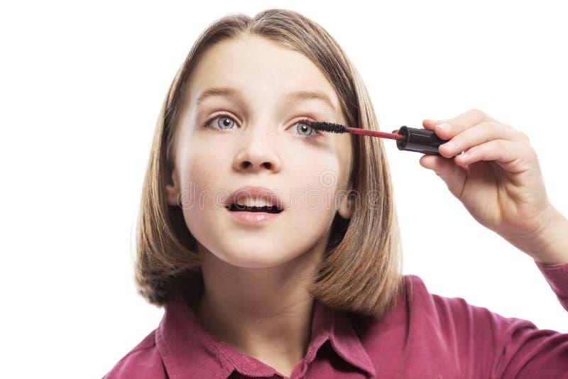 Cute teen girl paints eyelashes with mascara. Close-up. Isolated on a white background. Horizontal royalty free stock image