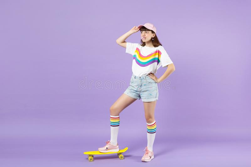 Cute teen girl in vivid clothes standing with yellow skateboard, blowing bubble gum, looking aside isolated on violet. Pastel background. People sincere royalty free stock photo