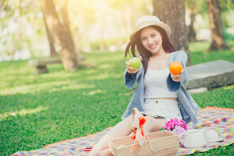 Cute teen giving fruit for eating healthy food when picnic stock images