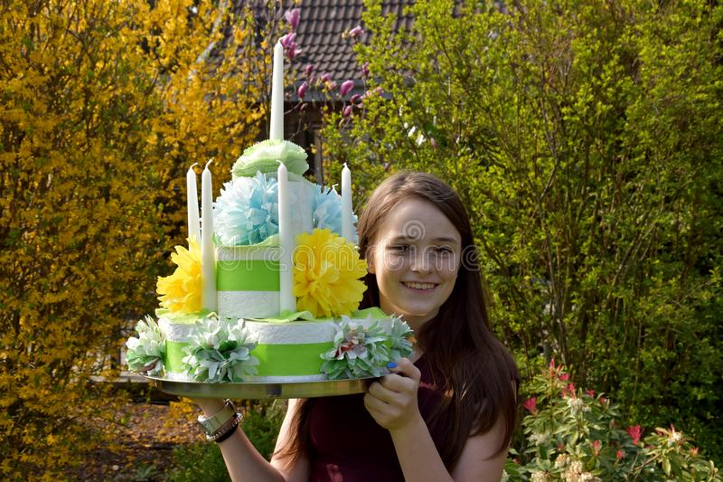 Girl brings birthday cake made of toilet paper. Cute teenage girl brings a gift, a birthday cake made of toilet paper rolls decorated with flowers of paper royalty free stock photography