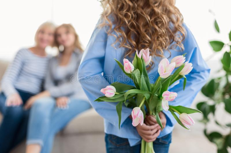 Cute teenage girl hiding flowers for her granny and mother stock photo