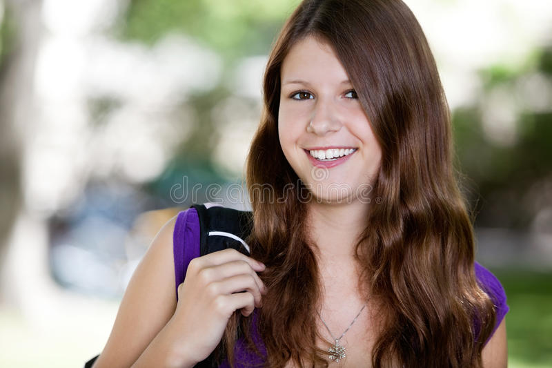 Cute teenage girl holding backpack royalty free stock photo