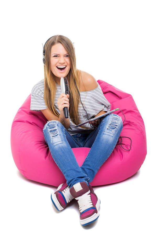 Cute teenage girl singing karaoke with hair brush microphone royalty free stock photo