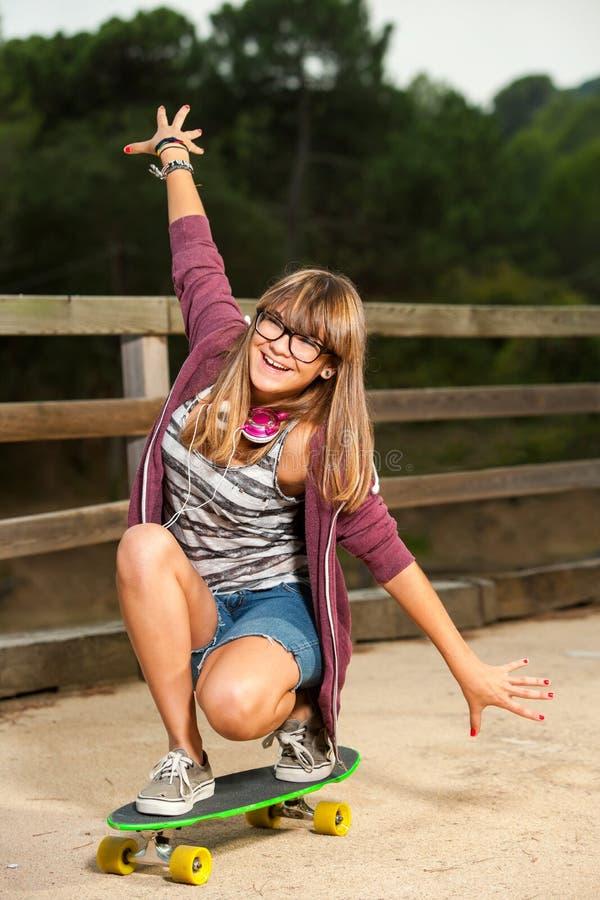 Cute teenage girl skateboarding. royalty free stock photo