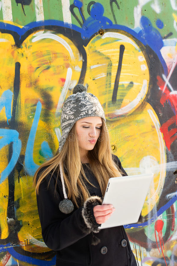 Cute teenage girl using tablet computer outdoors stock image