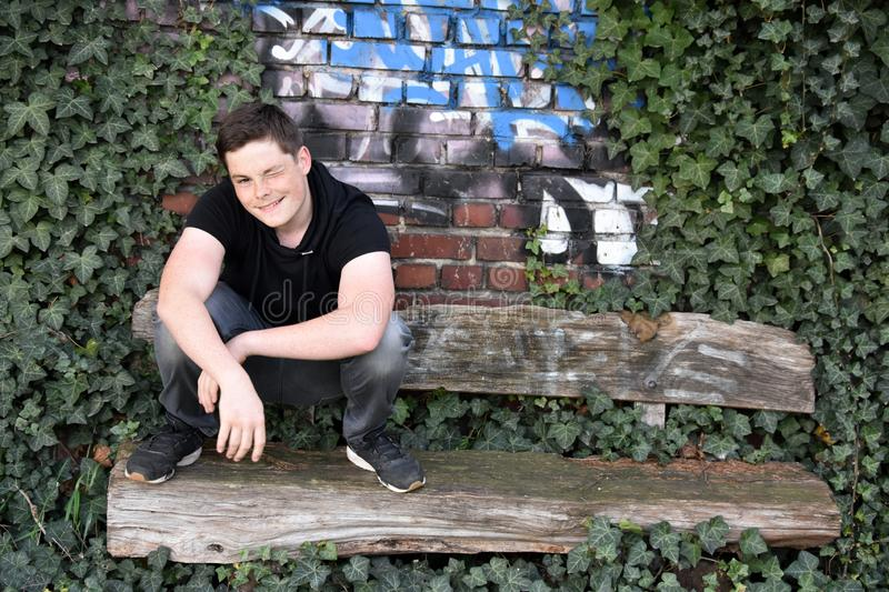 Teenage boy squats  outside  on old  bench. Cute teenager cowers on a bench overgrown with ivy in front of a graffiti wall stock images
