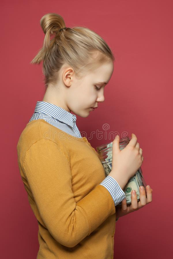Cute teenager girl holding money cash in jar. Students fees, responsibility and saving money concept stock photography