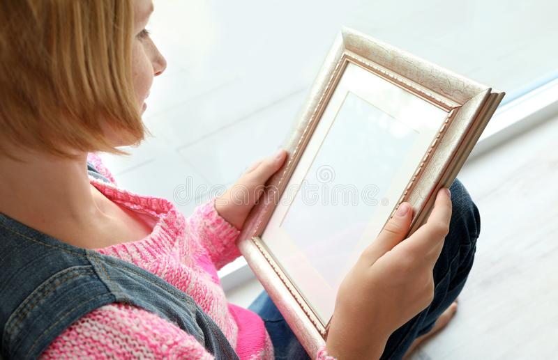 Teenager girl holding photo frame and sitting near window stock photography