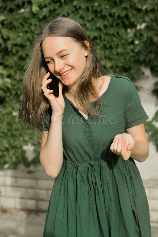 Cute teenager girl talking and smiling on mobile phone outdoors. Communication and education. Cute teenager girl talking and smiling on mobile phone outdoors royalty free stock photography