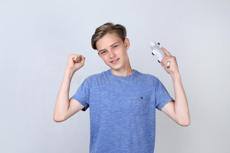 Teenager with joystick. Cute teenager with joystick on grey background stock photos