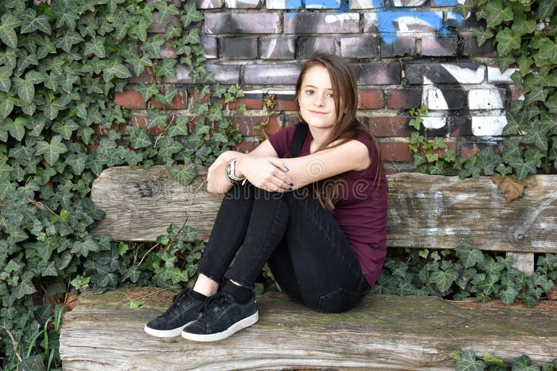Teenage girl resting outside  on old  bench. Cute teenager sitting on a bench overgrown with ivy in front of a graffiti wall royalty free stock photos