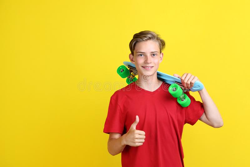 Teenager with skateboard. Cute teenager with skateboard on yellow background royalty free stock images