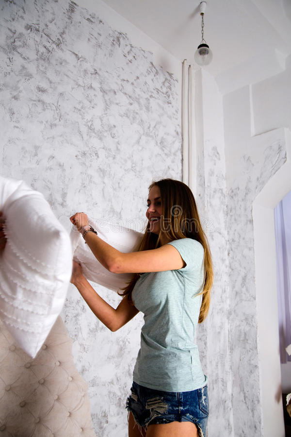 Cute teenagers fighting with pillows on the bed royalty free stock photo