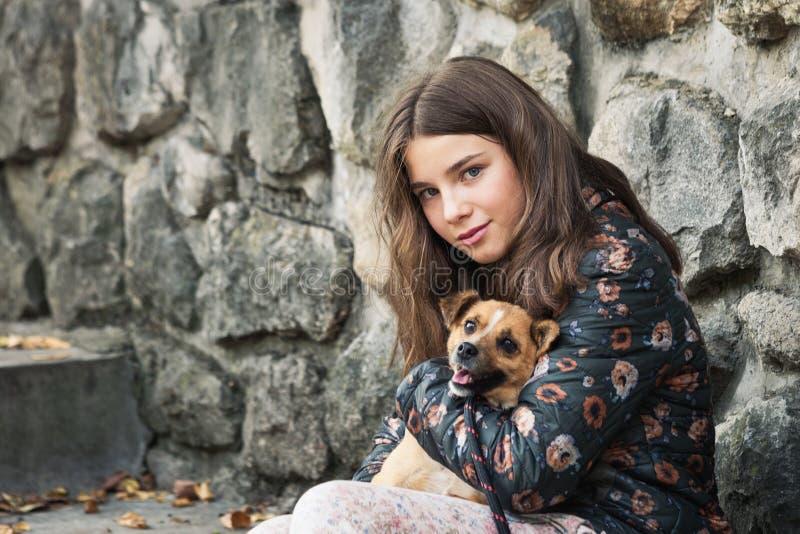 Cute Teeny Mädchen umarmte ihren neuen Haustier Adoptivhund aus dem Notunterkünfte stockbilder