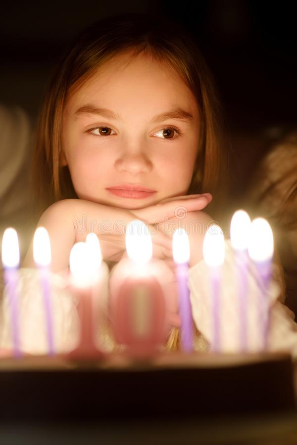 Cute ten year old girl making a wish before blowing candles on her birthday cake. Child celebrating her birhday royalty free stock images