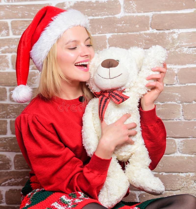 Cute and tender gift. Woman santa hat hug soft toy bear. Best gift ever. Girl happy celebrate new year christmas. Receive teddy bear as gift. Wish you merry royalty free stock photo
