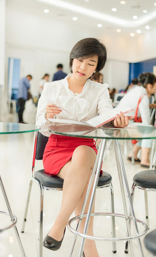 Cute Thai (Asian) businesswoman is reading her document file in royalty free stock images