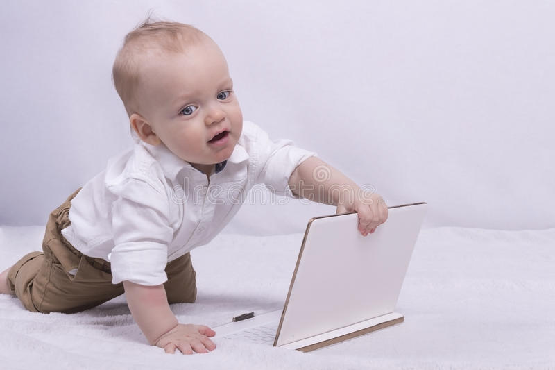 Cute thoughtful boy in white shirt playing with a tablet. Funny infant boy with laptop looks like little businessman royalty free stock image