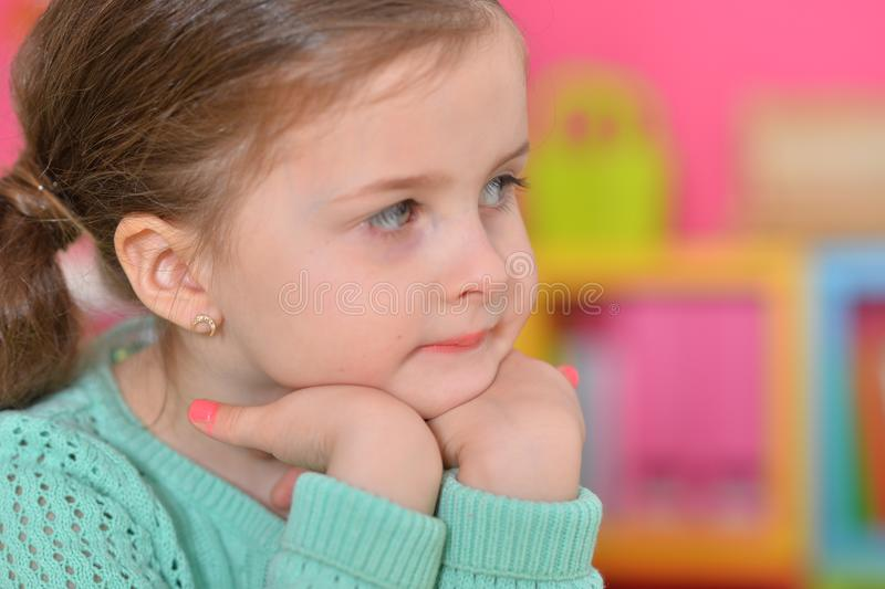 Cute thoughtful little girl posing at home stock images