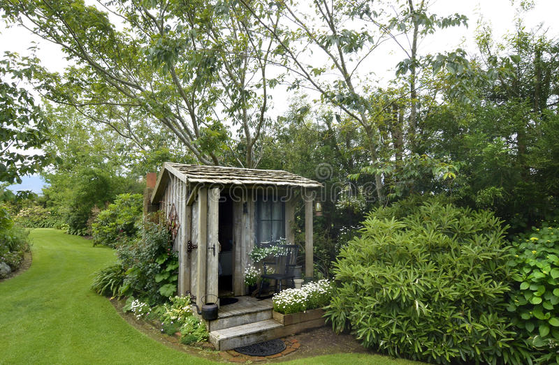 Cute tiny timber antique shack sitting in stunning flower garden royalty free stock photography