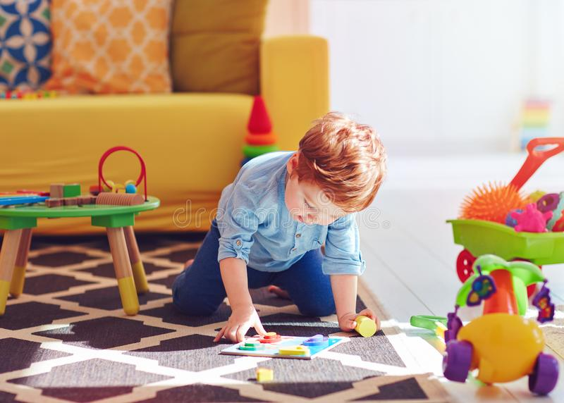 Cute toddler baby boy playing with toys on the carpet at home royalty free stock image