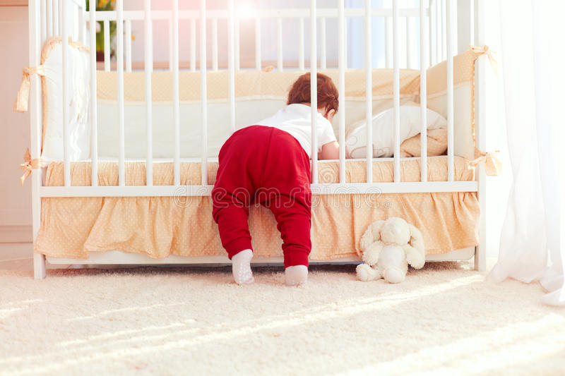 Cute toddler baby climbing into the cot in nursery room at home royalty free stock photos