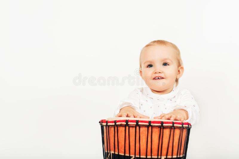 Cute toddler baby girl playing ethnic drum stock images