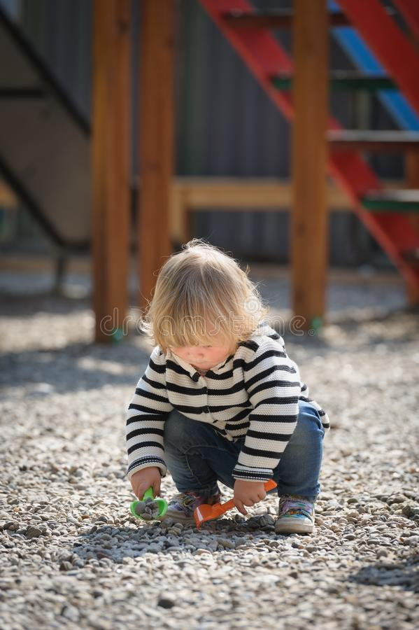 Cute toddler baby girl playing with shovel at playground stock photography